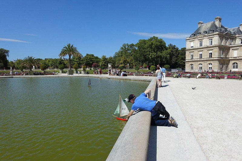 playing with a boat at jardin du luxembourg gardens by guilhem vellut