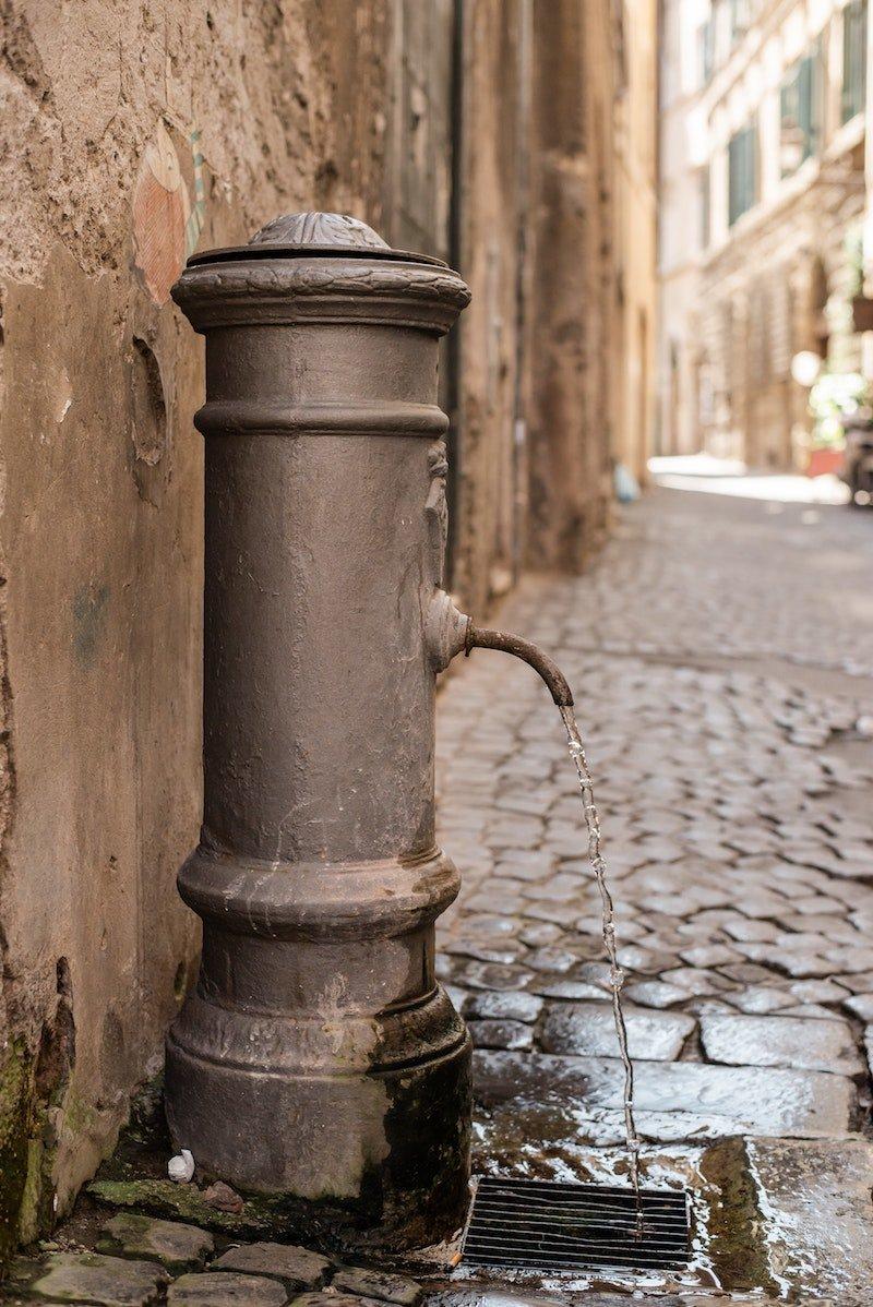 street-drinking-fountain-on-paved-narrow-sidewalk