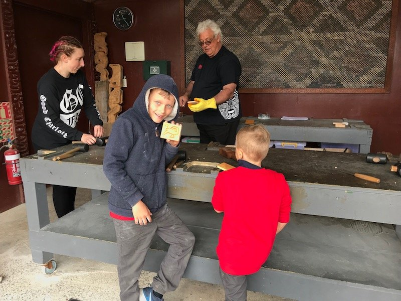 Photo- boys doing maori carving at hells gate thermal park
