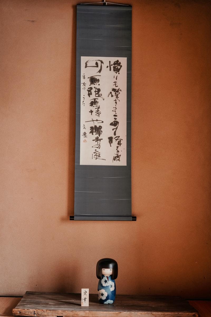 image - Japanese calligraphy art scroll and kokeshi doll by koto-kyoto unsplash